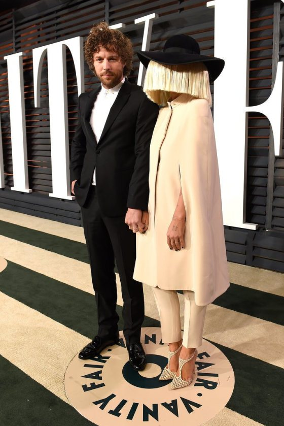 Sia (com o rosto escondido) e seu marido